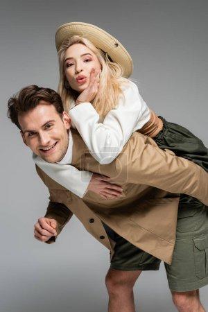 Photo pour Homme positif piggyback gai blonde femme isolé sur gris - image libre de droit