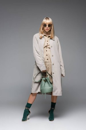 full length of fashionable young woman in sunglasses and trench coat posing with green bag on grey