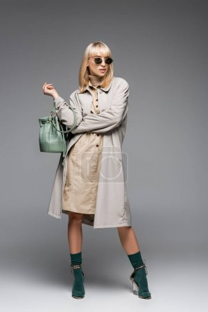 full length of fashionable woman in sunglasses and trench coat posing with green bag while standing on grey