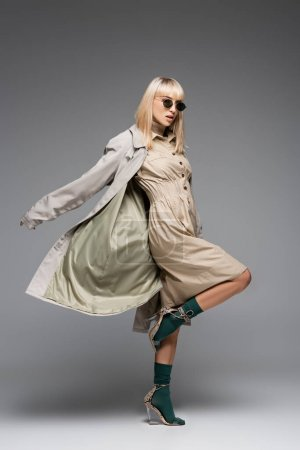 full length of fashionable woman in sunglasses and trench coat posing on grey
