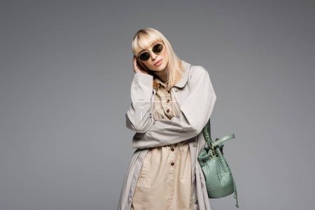 fashionable woman in sunglasses and trench coat posing with green bag while standing isolated on grey