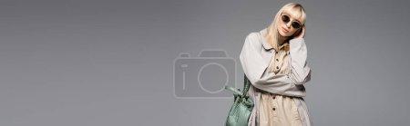 femme à la mode en lunettes de soleil et trench coat posant avec sac vert tout en étant isolé sur gris, bannière