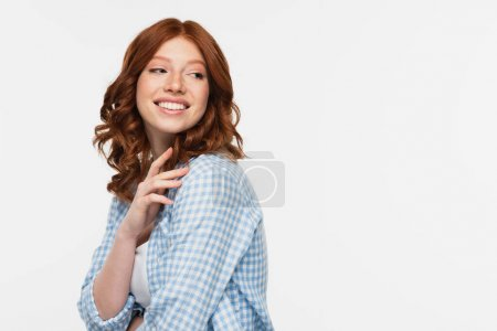 happy redhead young woman in blue checkered shirt looking away isolated on white