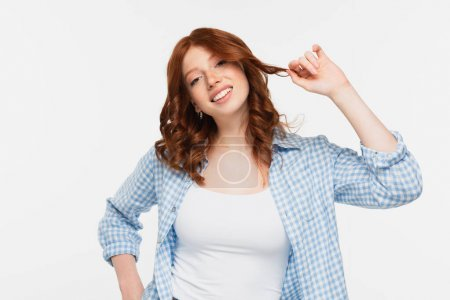 Photo for Happy young woman in blue checkered shirt adjusting curly red hair isolated on white - Royalty Free Image