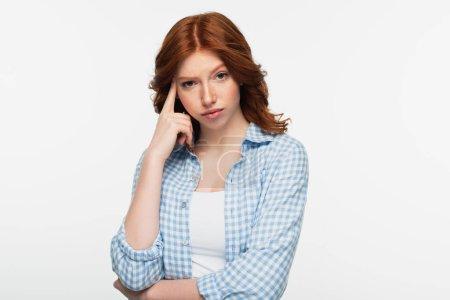 nachdenkliche rothaarige Frau im blau karierten Hemd isoliert auf weißem Grund