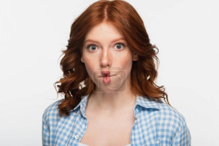 redhead woman in blue plaid shirt making fish face with lips isolated on white