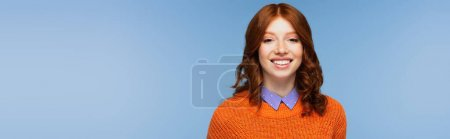 happy redhead woman in orange sweater isolated on blue, banner
