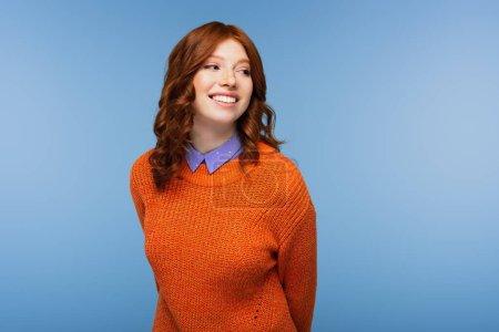 mujer pelirroja feliz en suéter naranja mirando hacia otro lado aislado en azul