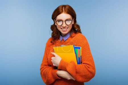smiling student in glasses and orange sweater holding notebooks isolated on blue