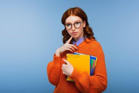 Photo pour Cher étudiant en lunettes et pull orange tenant des carnets isolés sur bleu - image libre de droit