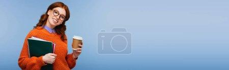 Photo pour Heureux rousse étudiant en lunettes et pull orange tenant des carnets et tasse en papier isolé sur bleu, bannière - image libre de droit