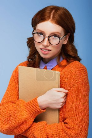 redhead student in glasses and orange sweater holding book isolated on blue