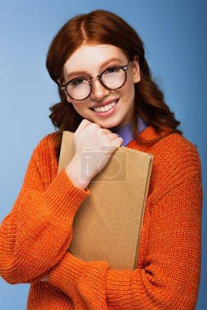 Photo pour Étudiant rousse souriant en lunettes et pull orange tenant livre isolé sur bleu - image libre de droit