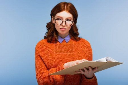 Photo for Redhead student in glasses and orange sweater holding book and looking away isolated on blue - Royalty Free Image