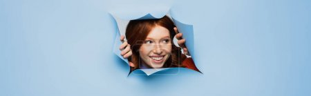cheerful redhead young woman looking away on blue ripped background, banner
