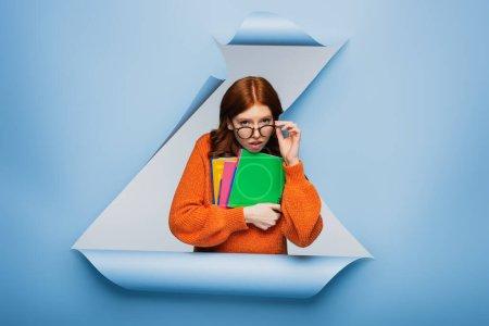 Photo pour Rousse jeune étudiante en pull orange ajustant les lunettes et tenant des carnets sur fond de papier bleu déchiré - image libre de droit