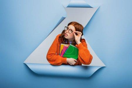 Photo pour Étudiante rousse en pull orange et lunettes tenant des carnets sur fond de papier bleu déchiré - image libre de droit
