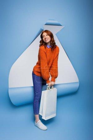 joyeuse rousse jeune femme tenant des sacs à provisions sur fond de papier bleu déchiré