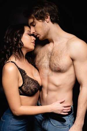 Photo for Brunette sexy woman in lace bra hugging with shirtless man isolated on black - Royalty Free Image