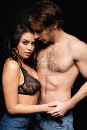 sexy Frau in Spitzen-BH hält Hände mit hemdlosem Mann isoliert auf schwarz