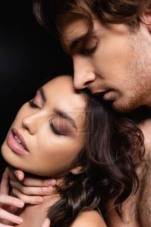 Photo for Passionate man touching neck of seductive woman isolated on black - Royalty Free Image