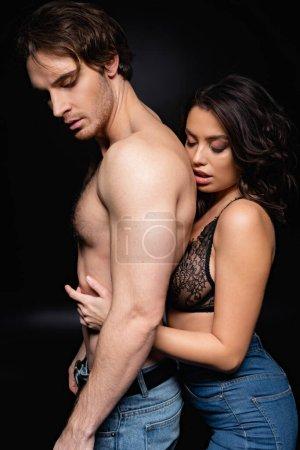 sexy woman in lace bra hugging shirtless man on black