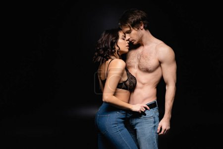 sexy woman and shirtless man in jeans hugging on black