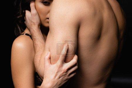 morena mujer mirando a la cámara y abrazando con el hombre sin camisa en negro