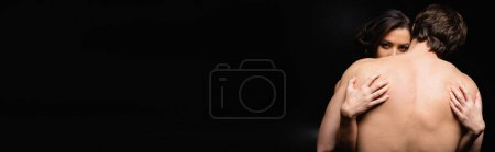 Photo for Back view of shirtless man hugging woman isolated on black, banner - Royalty Free Image