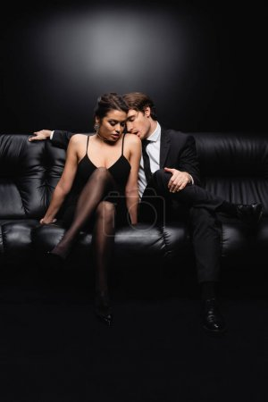 full length of passionate man in suit kissing shoulder of seductive woman in slip dress sitting on couch on black
