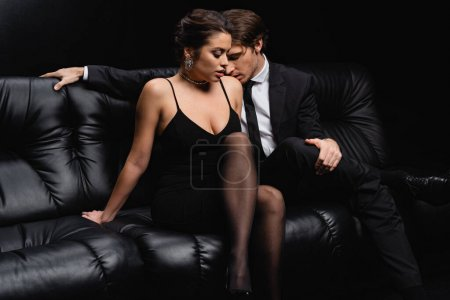 Photo for Passionate man in suit kissing shoulder of seductive woman in slip dress sitting on couch isolated on black - Royalty Free Image