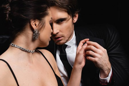 passionate man in suit holding hand of seductive woman in slip dress isolated on black