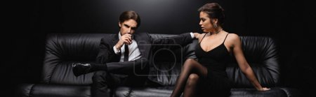 Photo for Man in suit sitting on leather sofa with glass of whiskey near woman in slip dress on black, banner - Royalty Free Image