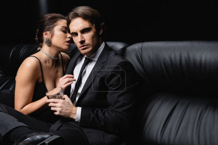 sexy woman in slip dress seducing man in suit holding glass of whiskey on black