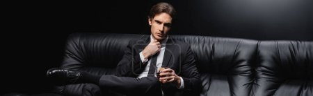 Photo for Elegant man in suit sitting on leather couch with glass of whiskey on black background, banner - Royalty Free Image