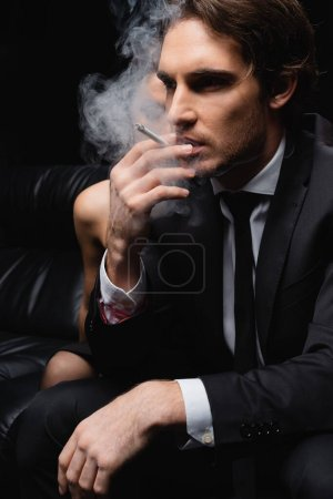 serious man in suit smoking cigarette near woman on blurred black background
