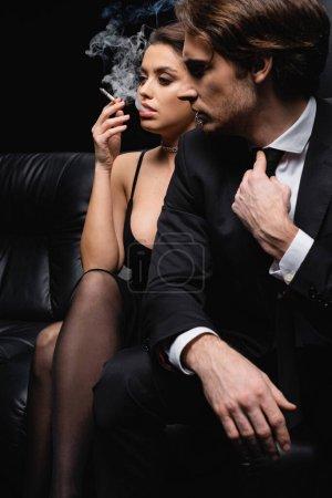 sexy woman in slip dress smoking cigarette near man sitting on black sofa