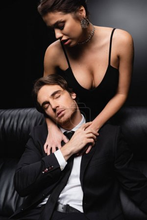 seductive woman in slip dress standing near man sitting on leather couch on black