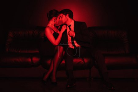red lighting on sexy couple hugging on black leather sofa