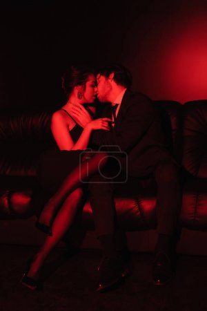 red lighting on sexy couple kissing on black leather sofa