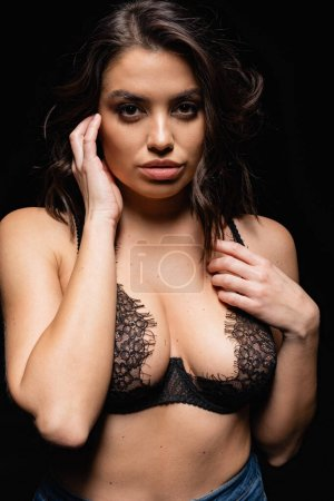 young brunette woman with big breast looking at camera isolated on black