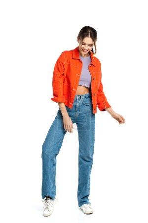 longitud completa de la joven feliz en la parte superior de la cosecha y camisa naranja de pie aislado en blanco
