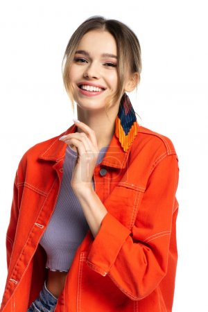 positive young woman in crop top and orange shirt isolated on white