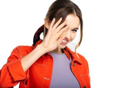 fröhliche junge Frau in orangefarbenem Hemd, die Gesicht bedeckt, Hand isoliert auf weiß