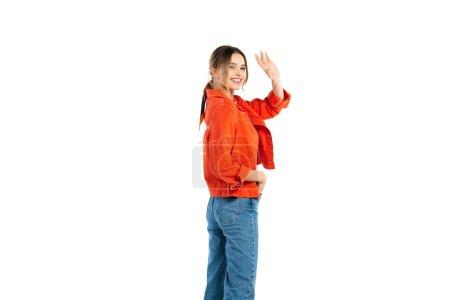 glückliche junge Frau in Jeans und orangefarbenem Hemd winkt Hand isoliert auf weißem Grund