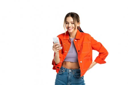 happy young woman in crop top and orange shirt using smartphone while standing with hand on hip isolated on white