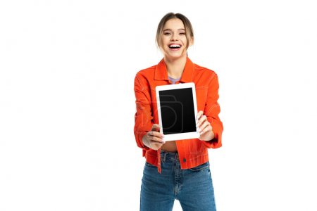 cheerful young woman in orange shirt and jeans holding digital tablet with blank screen isolated on white