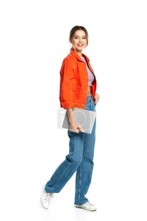 full length of happy young freelancer holding laptop isolated on white