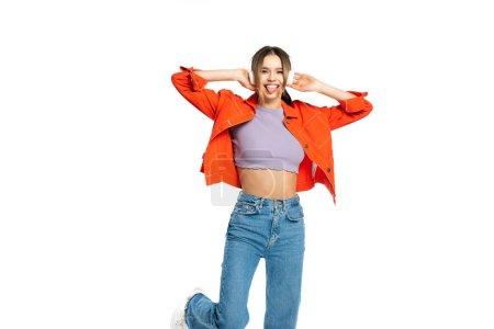 fröhliche Frau, die die Zunge herausstreckt, während sie Musik in drahtlosen Kopfhörern hört, isoliert auf weiß