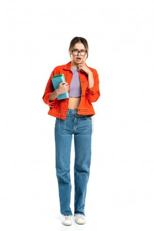 full length of surprised young student in glasses holding books isolated on white